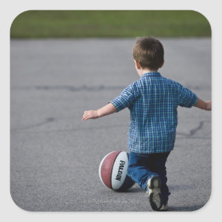 Boy chasing basketball outdoors square sticker