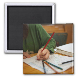 Boy concentrating on math homework 2 inch square magnet