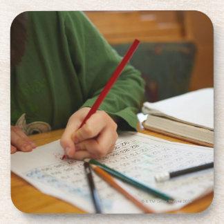 Boy concentrating on math homework beverage coaster