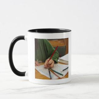 Boy concentrating on math homework mug
