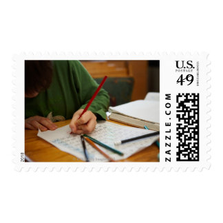 Boy concentrating on math homework postage