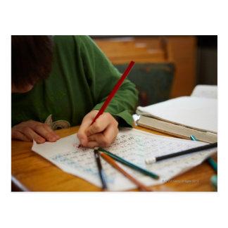 Boy concentrating on math homework postcard