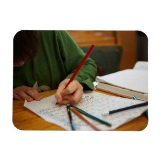 Boy concentrating on math homework magnet