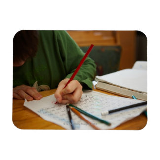 Boy concentrating on math homework rectangular photo magnet