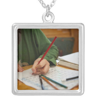 Boy concentrating on math homework silver plated necklace