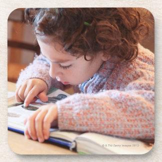 Boy concentrating on reading homework coaster
