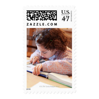 Boy concentrating on reading homework postage