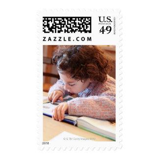 Boy concentrating on reading homework postage stamp