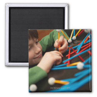 Boy connecting molecules for science project 2 inch square magnet