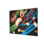 Boy connecting molecules for science project canvas print