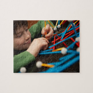 Boy connecting molecules for science project jigsaw puzzle