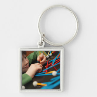 Boy connecting molecules for science project keychain