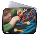 Boy connecting molecules for science project laptop computer sleeves