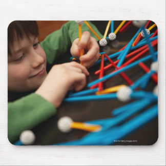 Boy connecting molecules for science project mouse pad