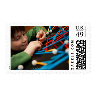 Boy connecting molecules for science project postage