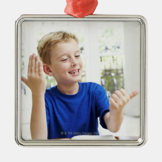 Boy counting on his fingers to complete his metal ornament