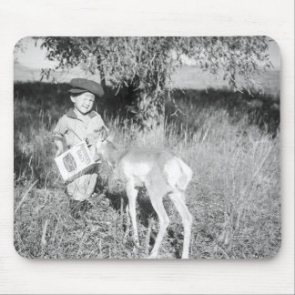 Boy feeding antelope by hand mouse pad