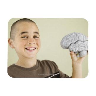 Boy holding human brain model magnet