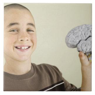 Boy holding human brain model ceramic tiles
