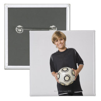 Boy holding soccer ball, smiling, portrait 2 inch square button