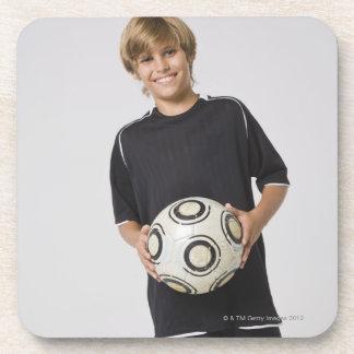 Boy holding soccer ball, smiling, portrait beverage coaster
