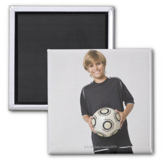Boy holding soccer ball, smiling, portrait magnet