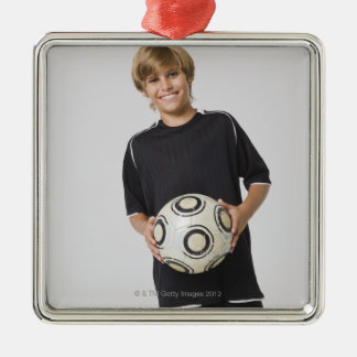 Boy holding soccer ball, smiling, portrait square metal christmas ornament