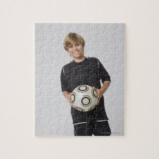 Boy holding soccer ball, smiling, portrait puzzle