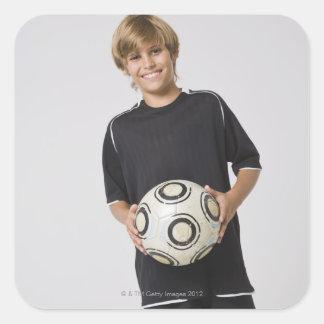 Boy holding soccer ball, smiling, portrait square sticker