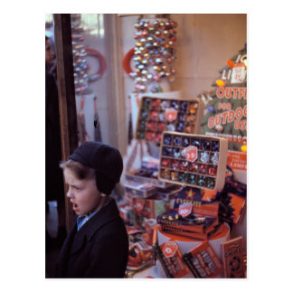 Boy in front of early 1940s Christmas Display Postcard