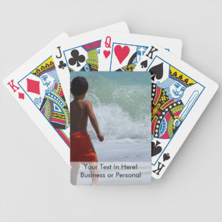 boy on beach playing in water bicycle playing cards