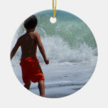 boy on beach playing in water christmas ornaments