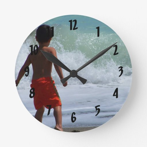 boy on beach playing in water clock