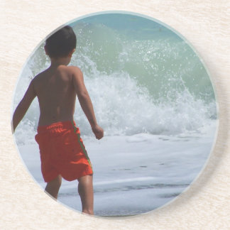 boy on beach playing in water coaster