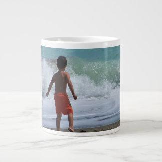 boy on beach playing in water giant coffee mug