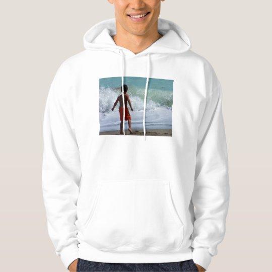 boy on beach playing in water hoodie