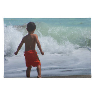 boy on beach playing in water placemat
