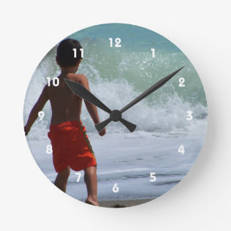 boy on beach playing in water round clock