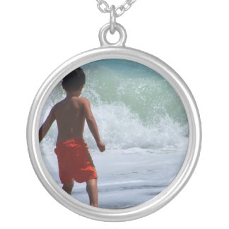 boy on beach playing in water round pendant necklace