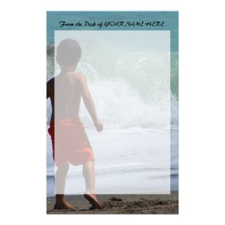 boy on beach playing in water stationery paper