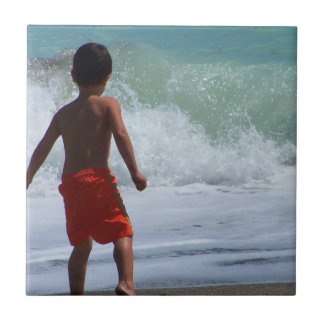 boy on beach playing in water tile