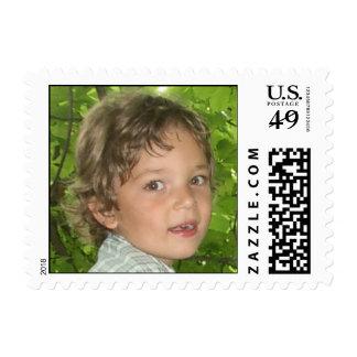 boy on green leaves postage stamp