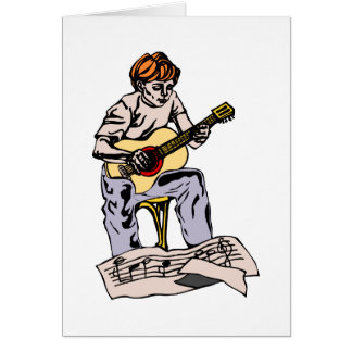 Boy playing acoustic guitar with sheet music card