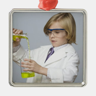 Boy pouring liquid into beaker metal ornament