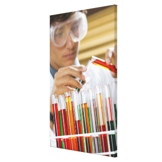 Boy pouring mixture from test tube canvas print