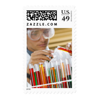 Boy pouring mixture from test tube postage stamps