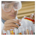 Boy pouring mixture from test tube large square tile