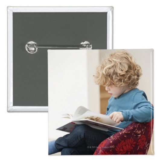 Boy reading a book pinback button