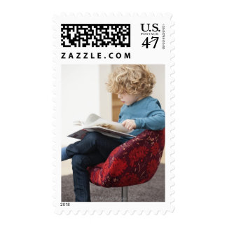 Boy reading a book postage stamp