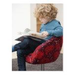 Boy reading a book postcard